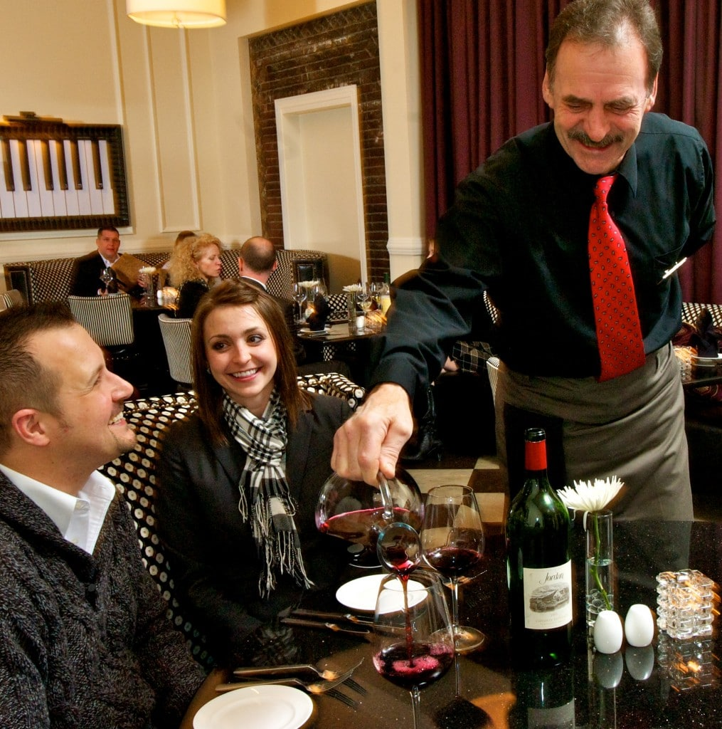 Waiter pouring wine for a couple at a restaurant table.